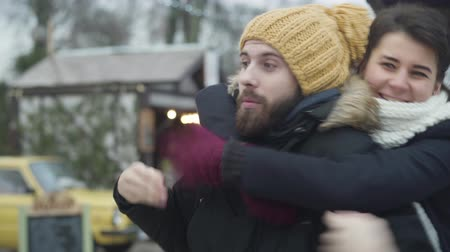 Handsome Caucasian man in yellow hat standing on winter street as his beautiful girlfriend or wife running up from background and hugging him. Happy couple having fun outdoors. Unity, relationship.