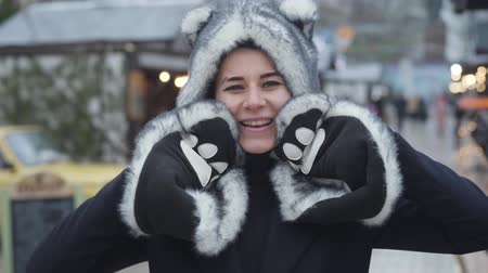 Portrait of cheerful Caucasian woman in wolf hat and gloves smiling and waving at camera. Happy young girl spending weekends on winter fair. Leisure, resting, lifestyle.