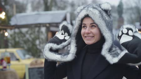 Funny Caucasian girl in fur animal hat and gloves looking at camera and smiling. Young cheerful woman waving. Happy lady spending weekends outdoors. Leisure, resting, lifestyle.