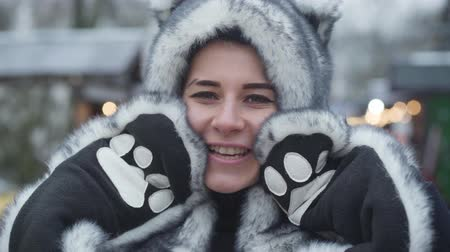 Close-up face of smiling Caucasian girl in fur animal hat and gloves looking at camera. Portrait of young beautiful woman spending weekends outdoors. Leisure, resting, lifestyle.