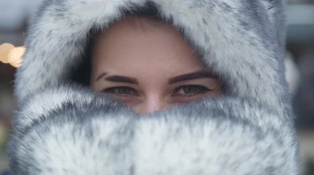 adil : Extreme close-up eyes of beautiful Caucasian girl. Pretty young woman with brown eyes hiding face in fur hat and scarf. Lifestyle, beauty, happiness. Stok Video