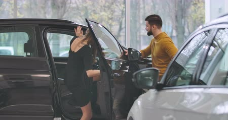 seçme : Young Caucasian family standing in car dealership next to black automobile and talking. Woman getting into salon. Successful man buying vehicle for wife. Car business. Cinema 4k footage ProRes HQ. Stok Video