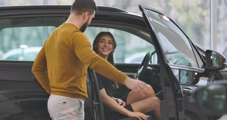 satın almak : Young Caucasian man in mustard sweater opening car door and talking to beautiful girl sitting in car salon. Couple choosing new vehicle in car dealership. Car business. Cinema 4k footage ProRes HQ.