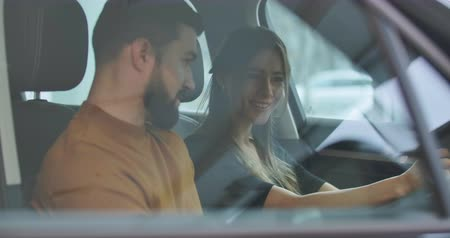 exito : Side view of young Caucasian family sitting in car salon and talking. Husband and wife choosing new automobile in car dealership. Car business. Cinema 4k footage ProRes HQ.