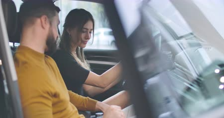 kierowca : Side view of young Caucasian girl looking with love at her husband as sitting in car salon. Husband and wife choosing new automobile in car dealership. Car business. Cinema 4k footage ProRes HQ.