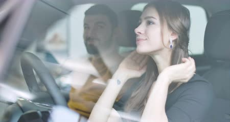 임대의 : Shooting through car side window of beautiful Caucasian girl sitting in salon and talking with her boyfriend or husband. Young woman choosing automobile in car dealership. Cinema 4k footage ProRes HQ.