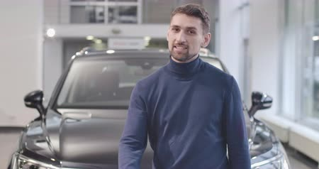 kciuk : Portrait of young Caucasian man standing in front of new car and showing thumb up. Satisfied client happy with the purchase of new vehicle. Car dealership, car business. Cinema 4k footage ProRes HQ. Wideo