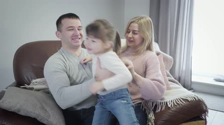 kapcsolat : Portrait of cute little Caucasian girl sitting on mothers hands, then hugging father. Cheerful young family enjoying free time at home together. Leisure, happiness, parenthood. Stock mozgókép