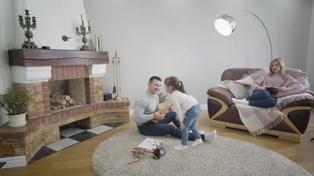 passatempo : Smiling blond Caucasian woman sitting on armchair with tablet and looking at her husband playing ukulele and daughter dancing around him. Cheerful young family enjoying free time together indoors. Vídeos
