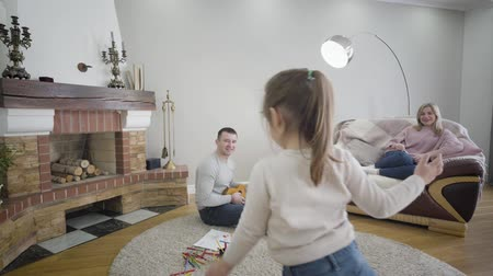 Portrait of playful Caucasian brunette girl dancing as her father playing ukulele and mother sitting on couch at the background. Cheerful cute child leaving shot to the left. Family, unity, leisure. 影像素材