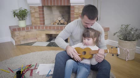 lesgeven : Portrait of young Caucasian handsome man teaching daughter to play ukulele. Pretty little girl spending weekends with father at home. Leisure, hobby, lifestyle.