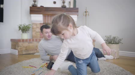 Close-up of pretty brunette Caucasian girl playing with toys as her smiling father talking to her at the background. Young man spending free time with daughter on weekends. Leisure, lifestyle, joy.