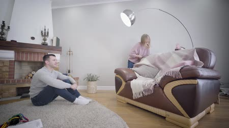 kapcsolat : Young Caucasian family enjoying weekends indoors. Man sitting on soft carpet in front of fireplace as his wife playing hide-and-seek with daughter. Leisure, fun, joy.
