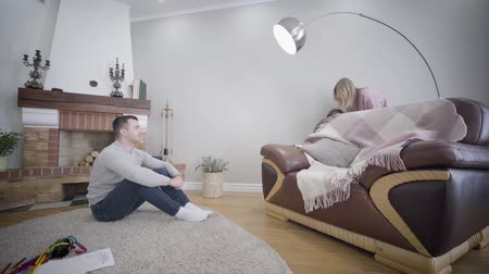 скрывать : Side view of young Caucasian man sitting in front of fireplace and looking at his wife and daughter playing hide-and-seek. Mother leading pretty girl to armchair. Lifestyle, family, weekends. Стоковые видеозаписи