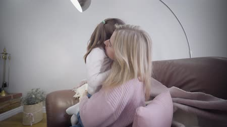 kapcsolat : Side view of young Caucasian beautiful woman sitting on armchair at home and playing with daughter. Happy mother hugging her child and talking. Unity, happiness, lifestyle.