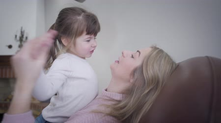 barátságos : Close-up of cute little Caucasian brunette girl playing with beautiful blond mother at home. Cheerful young woman having fun with daughter indoors. Happiness, leisure, unity.