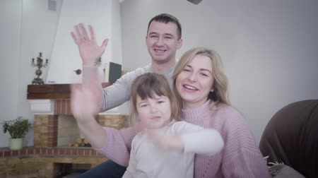 Portrait of happy young Caucasian family waving at camera. Smiling man, woman, and little girl sitting on armchair indoors. Lifestyle, joy, happiness.