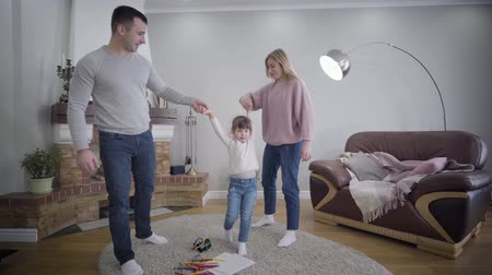vychovávat : Young Caucasian husband and wife holding daughters hands and raising child up. Playful positive family enjoying time together indoors. Unity, lifestyle, happiness.