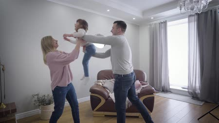 objetí : Cheerful Caucasian young man spinning with daughter and giving her to beautiful blond wife. Camera zooming in to faces of happy hugging family looking at camera and smiling. Joy, happiness, lifestyle. Dostupné videozáznamy