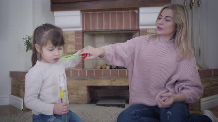 Beautiful young Caucasian woman helping little cute girl to blow soap bubbles. Blond cheerful mother spending weekends with adorable daughter at home. Unity, leisure, happiness. 影像素材