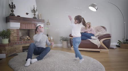Smiling Caucasian man blowing soap bubbles, his cute little daughter jumping up, and beautiful blond wife sitting on armchair with book. Happy young family enjoying weekends indoors. Leisure, joy.