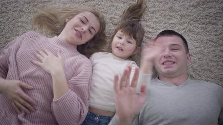 блондин : Top view close-up of smiling Caucasian family lying on soft carpet and waving at camera. Portrait of happy father, mother and daughter. Lifestyle, unity, happiness.