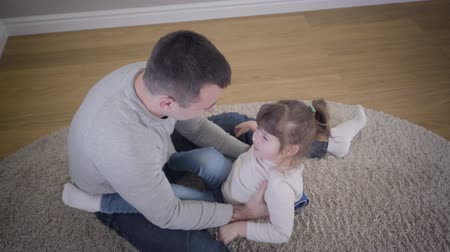 przystojny mezczyzna : Top view of pretty brunette Caucasian girl playing with father at home. Young man having fun with daughter sitting on soft carpet indoors. Leisure, unity, lifestyle.
