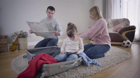 podróż : Young Caucasian family packing suitcase before trip. Man looking at map, woman folding clothes, little girl sitting in travel bag and using smartphone. Tourism, lifestyle, unity.