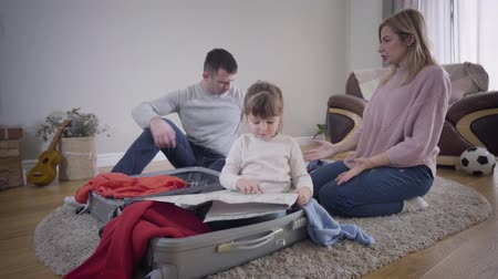 Portrait of happy young parents packing travel bag as their daughter examining map at the foreground. Cheerful man and woman putting different hats on childs head. Lifestyle, fun, tourism.