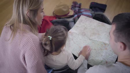 podróż : Back top view of young Caucasian family looking at map. Friendly father, mother and daughter making route for travel. Tourism. lifestyle, happiness.