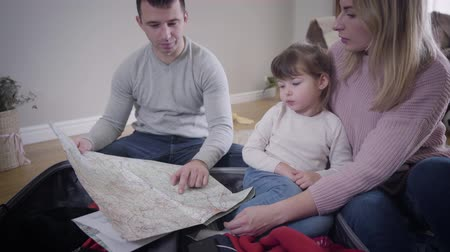 travelling : Portrait of happy young Caucasian family making route for future trip. Smiling young man, woman, and little pretty girl sitting together at home and looking at map talking. Tourism, travelling.