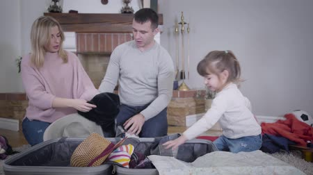 podróż : Timelapse of young cheerful Caucasian family packing clothes into travel bag. Father and mother putting stuff in, little playful girl taking them out, then helping parents to put all things back. Wideo