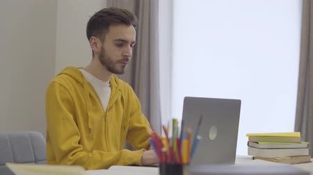 tiredness : Portrait of confident young Caucasian man working with laptop, yawning and putting head on table. Tired bearded student studying indoors. Education, exhaustion, lifestyle. Stock Footage