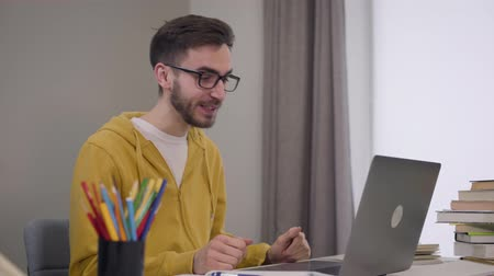 vista lateral : Handsome confident Caucasian boy in elegant eyeglasses sitting at the table and having video chat. Male student using laptop to study online. Education, modern technologies.