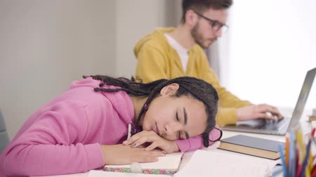 африканский : Close-up portrait of young beautiful African American girl sleeping at the table as smart Caucasian boy in eyeglasses typing on laptop at the background. Students overworking in university.