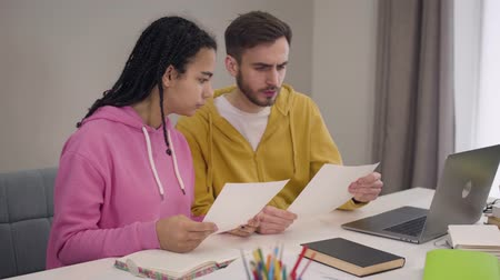 írás : Young university students sitting at the table with papers and talking to each other. Serious smart African American girl and Caucasian boy studying together. Lifestyle, intelligence, education.