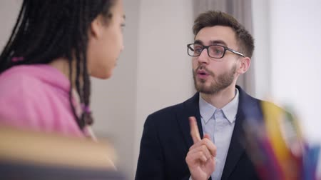 африканский : Young brunette Caucasian man with grey eyes talking to African American girl. Elegant teacher in suit and eyeglasses explaining education process to female student. Lifestyle, tutoring, studying.