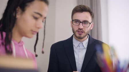 özel öğretmen : Close-up of strict male Caucasian teacher scolding young African American university student. Blurred sad girl at the foreground listening to tutor carefully. Education, problems, diligence.