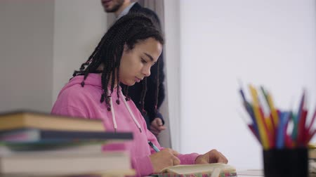 vista lateral : Side view portrait of attractive African American girl writing down as young Caucasian teacher in suit walking at the background and dictating. College, university, studying.