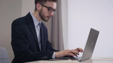 vista lateral : Side view portrait of handsome Caucasian businessman in eyeglasses typing on laptop. Young intelligent man in elegant suit working online. Lifestyle, working, intelligence. Stock Footage