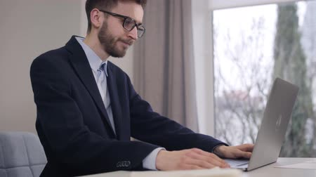praca : Portrait of young handsome Caucasian man looking out the window and typing on laptop keyboard. Confident businessman in suit and eyeglasses working online. Lifestyle, intelligence, wealth.