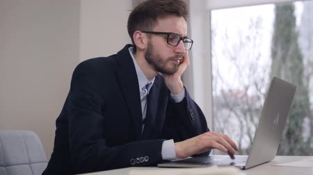 praca : Young tired Caucasian businessman holding head with hand and typing on laptop keyboard. Bored handsome man taking off eyeglasses and putting them on the table. Business, work, freelance.
