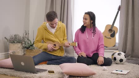 kapcsolat : Portrait of positive multiethnic couple playing ukulele and singing at home. Smiling young African American girl and Caucasian boy having fun together on weekends. Lifestyle, music, hobby.