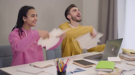 африканский : Portrait of cheerful multiethnic students throwing up papers and laughing. Happy African American girl and Caucasian boy having fun while studying. Happiness, education, lifestyle. Slow motion.