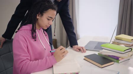 írás : Stressed sad African American girl sitting at the table as her Caucasian tutor standing by the table and talking. Nervous female student writing down in workbook. Education, stress, intelligence.