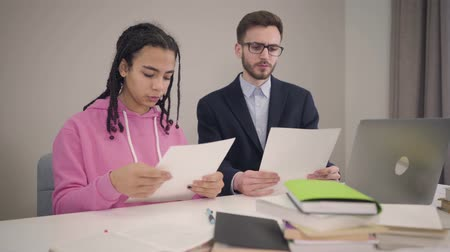 foco : Camera approaching slowly to African American girl and Caucasian boy looking through documents. Young students helping papers and talking with each other. Lifestyle, intelligence, education. Archivo de Video
