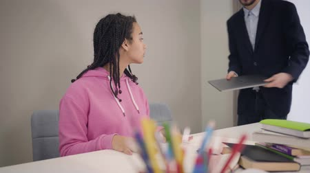 studente : Portrait of young African American girl sitting at the table as Caucasian teacher in suit coming up and shaking her hand. Student welcoming tutor indoors. Education, teaching, studying. Filmati Stock