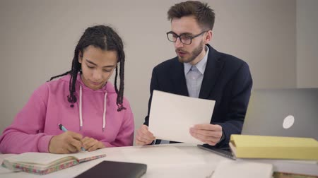 африканский : Camera approaching to intelligent Caucasian man in eyeglasses dictating and young African American girl writing in workbook. Cheerful tutor and student giving high five and smiling. Стоковые видеозаписи
