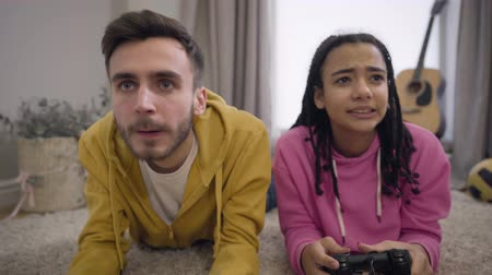 przystojny mezczyzna : Camera zooming in and moving up showing two cheerful friends using gaming console, giving high five and smiling. Happy Caucasian boy and African American girl winning in video game.