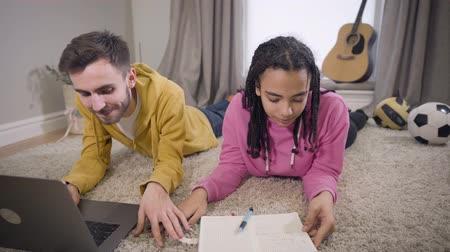 studente : Concentrated African American girl writing and putting hand on floor as Caucasian boy touching her palm and smiling. Young students in love doing homework together indoors. Lifestyle, happiness.